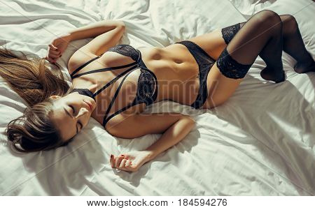 Beautiful brunette model with perfect body lying on her bed in black lace lingerie.
