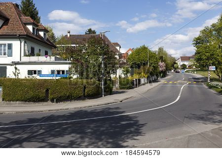 Bern Switzerland - April 14 2017: Residential houses among many bushes and trees in a quiet narrow street in a district away from the city center. Several people in a far distance can be seen.