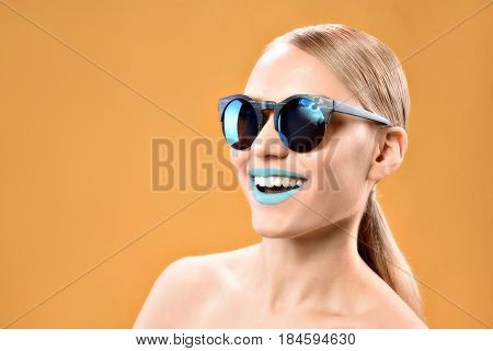 Showing her beauty. portrait of trendy young woman wearing shades and smiling happily with copy space in left side