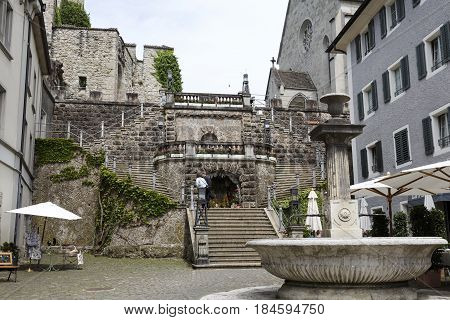 Rapperswil Switzerland - May 10 2016: Staircase that leads to a Castle. On a small square on the sidewalk the large fountain has placed