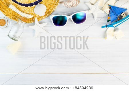 Summer Beach accessories (White sunglassesstarfishstraw hatglass bottleshell) on white plaster wood table top viewSummer vacation conceptLeave space for adding text.