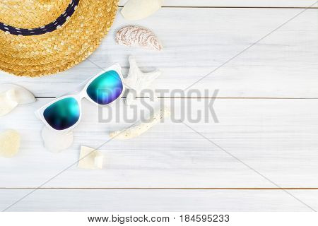 Summer Beach accessories (White sunglassesstarfishstraw hatshell) on white plaster wood table top viewSummer vacation conceptLeave space for adding text.
