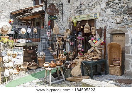 Yvoire France - May 24 2013: The store outside a historical house that was built of stone can be seen along the street in medieval town. There are many wicker items but other items are also available