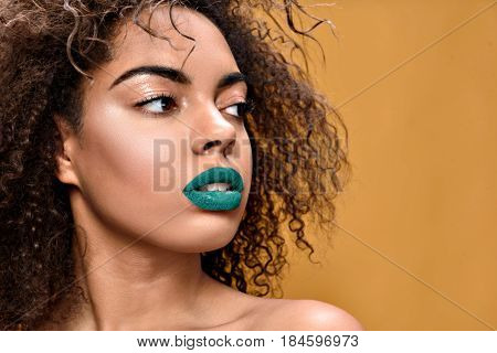 She has perfect look. portrait of attractive ethnic female with green lipstick standing and posing with copy space in right side