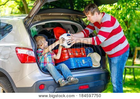 Adorable little kid boy sitting in car trunk just before leaving for summer vacation. Dad packing suitcases. Happy family going on long journey. happy family traveling. Summer travel.
