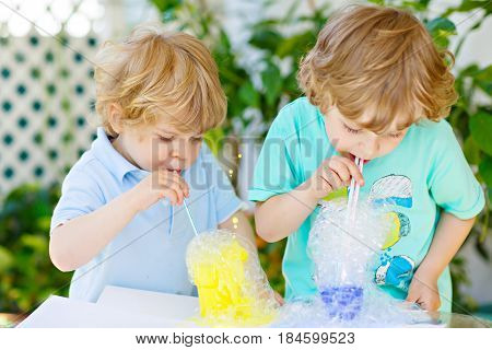 Two little boys making experiment with colorful soap bubbles and water, outdoors. Kids, best friends and siblings having fun with making and blowing bubbles.