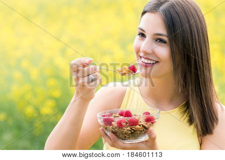 Close up portrait of attractive healthy young woman eating crispy whole grain cereal breakfast outdoors. Girl holding bowl with cereal and spoon against colorful yeller flower field.
