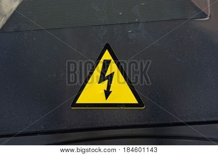 Close up of yellow high voltage sign on dark black surface