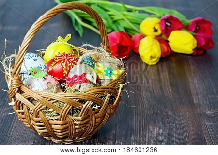 Easter eggs and tulips. Festive decoration on wood background. Holiday card with copy space.