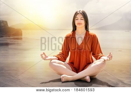 Portrait of young woman meditating at riverside. Girl sitting with eyes closed on sand against dreamy sunset background.