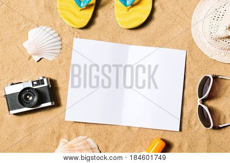 Summer vacation composition with pair of yellow flip flop sandals, hat, sunglasses, sun cream, empty paper sheet and other stuff on a beach. Sand background, studio shot, flat lay. Copy space.