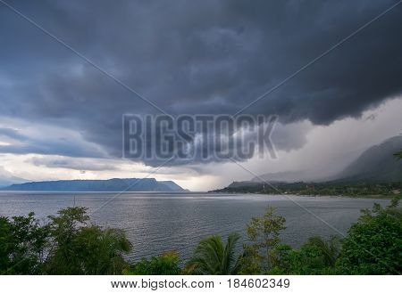 Lake Toba from Tuk-Tuk panoramic indonesian landscape with dramatic cloudy sky with heavy rain North Sumatra Indonesia