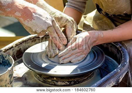 Close up hands working on pottery wheel crafting bowl in sunlight