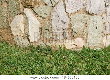The wall of natural stone. Rocks stone wall and green grass texture background.