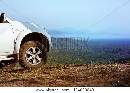 Big 4x4 car at top of mountain. Closeup photo of big car offroad wheel. Space for text