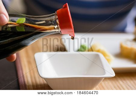 Close up pouring soy sauce in white bowl before eating Japanese food in restaurant