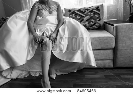 Bride In Wedding Dress Putting On Stockings Silk Garter, Wedding Morning Preparation Concept. Gettin
