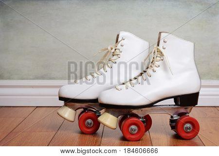 pair women white quad roller skates on hardwood floor