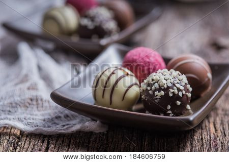 Decorated chocolate truffles on rustic wood with cheesecloth