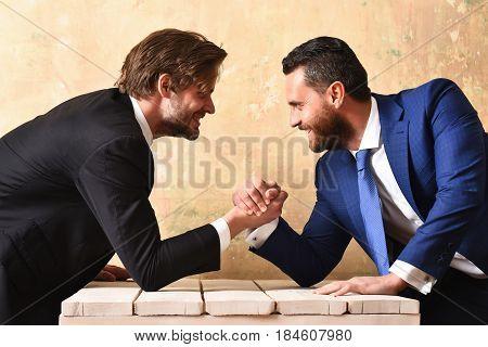 Challenge teamwork concept. Businessmen arm wrestling. Partners in suits.