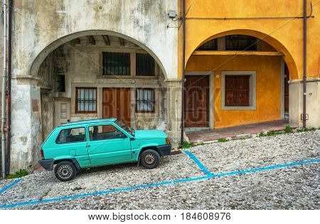 Vittorio Veneto (Veneto region) - December 2015, Italy: Green car parked by the old house with arcs, one of the streets of Vittorio Veneto - city and comune situated in the Province of Treviso
