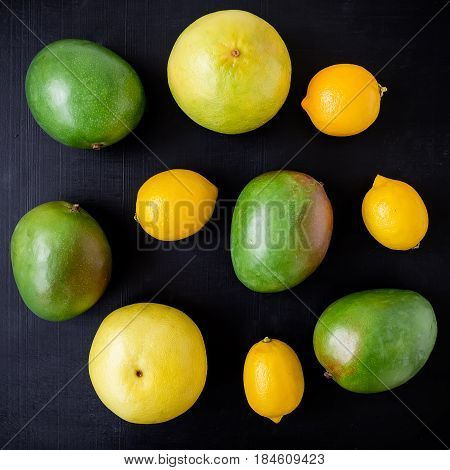 Citrus fruits, lemons, sweetie and mango on dark background. Flat lay, top view. Fruit colorful background.