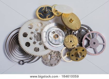 Pile of metal and plastic gears and sprockets on white background