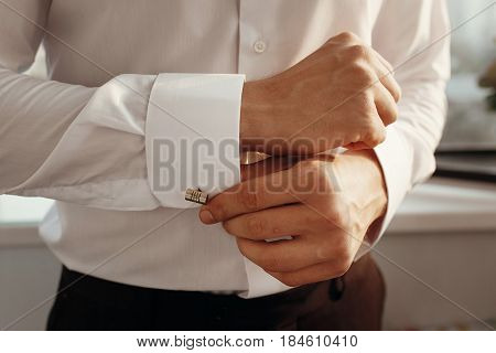 Stylish Groom Getting Ready In Morning, Putting On White Shirt Golden Cufflinks. Morning Preparation
