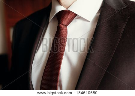 Stylish Groom Getting Ready In Morning, Putting On Brown Suit White Shirt And Red Tie Close Up. Morn