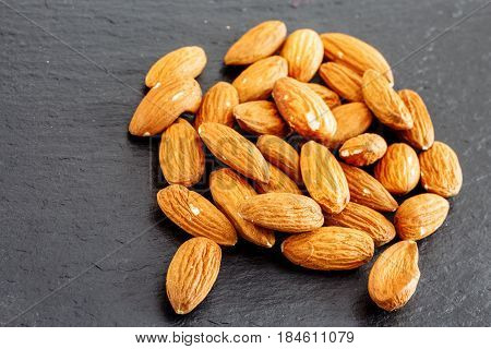 Group Of Almonds Isolated On A Black Slate Background