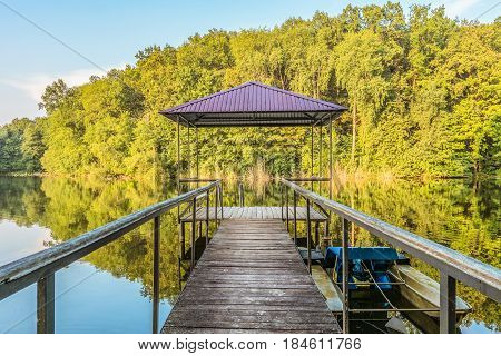Small wooden pier for pleasure pedal catamaran on the forest lake shore. Dock for pedal boat and a quiet holiday in nature. Disappearing into the distance perspective.