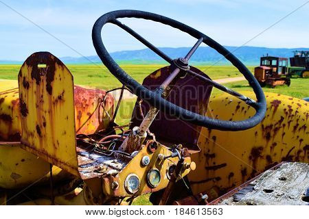 Vintage rusty farming tractor equipment taken on a rural forgotten prairie landscape in the Carrizo Plain, CA