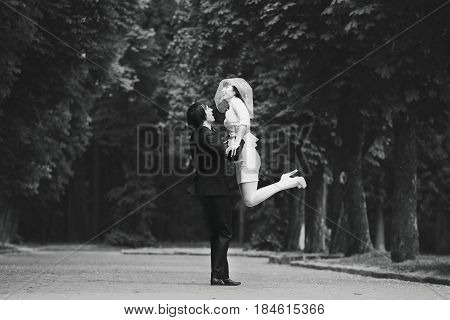 Black And White Picture Of A Handsome Fiance Raising Bride In Short Dress Up