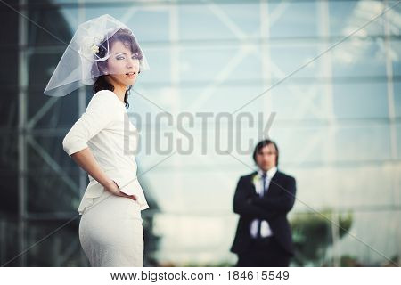 Stylish Modern Bride Looks Over Her Shoulder While Fiance Waits On The Background