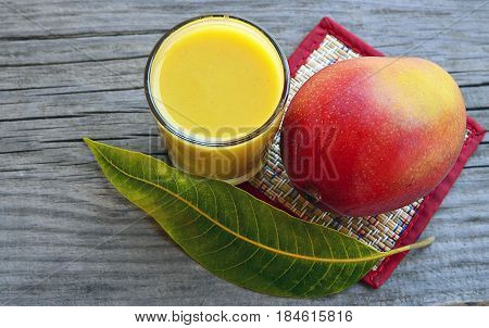 Save Download Preview Fresh mango smoothie,ripe mango fruit and mango tree leaf on old wooden table background.Healthy food,diet or vegan food concept.