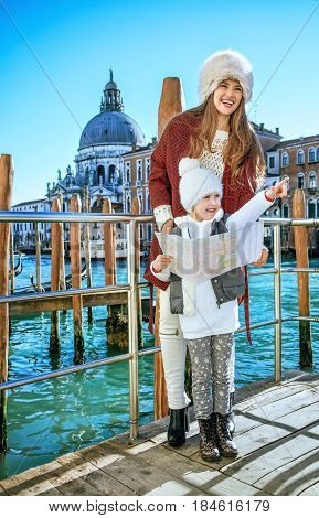 Mother And Child Tourists In Venice Holding Map And Pointing