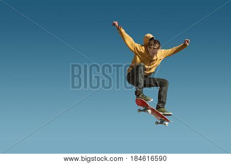 A teenager skateboarder does an ollie trick in a skatepark on the outskirts of the city On a background of blue sky gradient