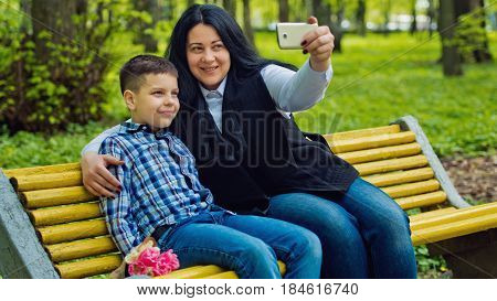 Mom and son in the park on a yellow bench are photographed selfies on a mobile phone. Family photo session.