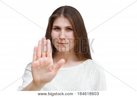 Portrait of a young brunette woman in a light jumper looking directly at the camera and showing stop gesture isolated on white background. Focus on the face. Demonstration of various emotions.