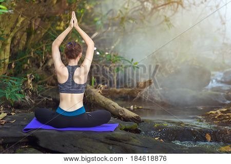 A woman yoga in water fall nature