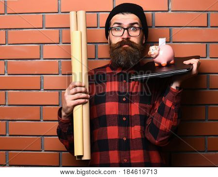 Bearded man long beard. Brutal caucasian surprised unshaven hipster holding craft paper rolls piggy bank on laptop in checkered shirt with hat and glasses on brown brick wall studio background