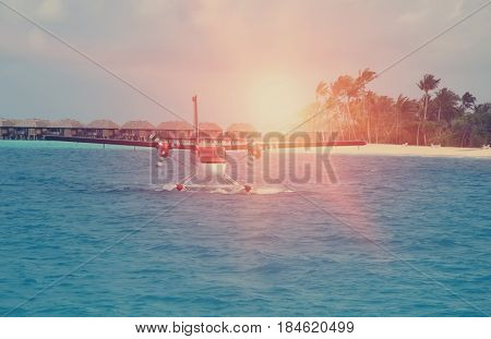 Seaplane at the sea near the island with palm trees retro effect