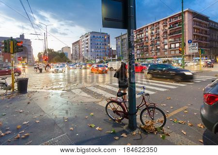 MILAN ITALY - September 06 2016: Red colored bicycle parked (fastened by lock) to the street pole lighting on the street of Milan on the evening and blurred cars' moving on the street.