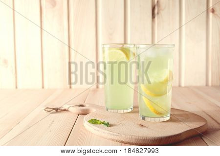 Citrus Lemonade Water With Lemon Sliced , Healthy And Detox Water Drink In Summer On Wooden Table .