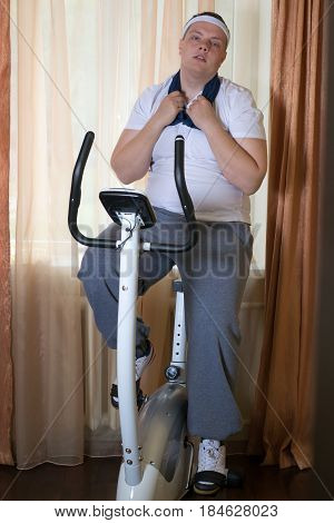 Fat guy exercising on stationary training bicycle at home