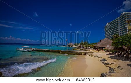 COZUMEL, MEXICO - MARCH 23, 2017: Beautiful vacation resort of Cozumel with some natural buildings and yachts, gorgeous blue ocean and sky.