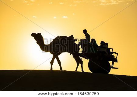 Jaisalmer, India - March 13, 2016: Rajasthan travel background - camel silhouette with the wagon in dunes of Thar desert on sunset. Jaisalmer, Rajasthan, India