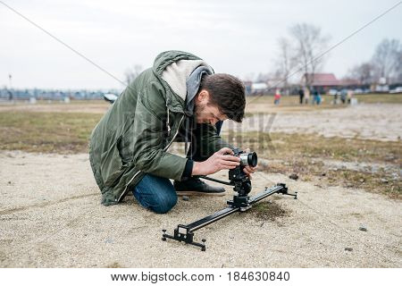 The cameraman shoots on the camera, outdoors. Sits on his knees and look into the lens