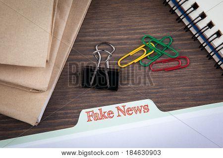 Fake News Infomation concept.Folder Register on a dark wooden desk.