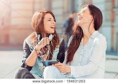 Two smiling young women with headphones listening to music from smart phone.